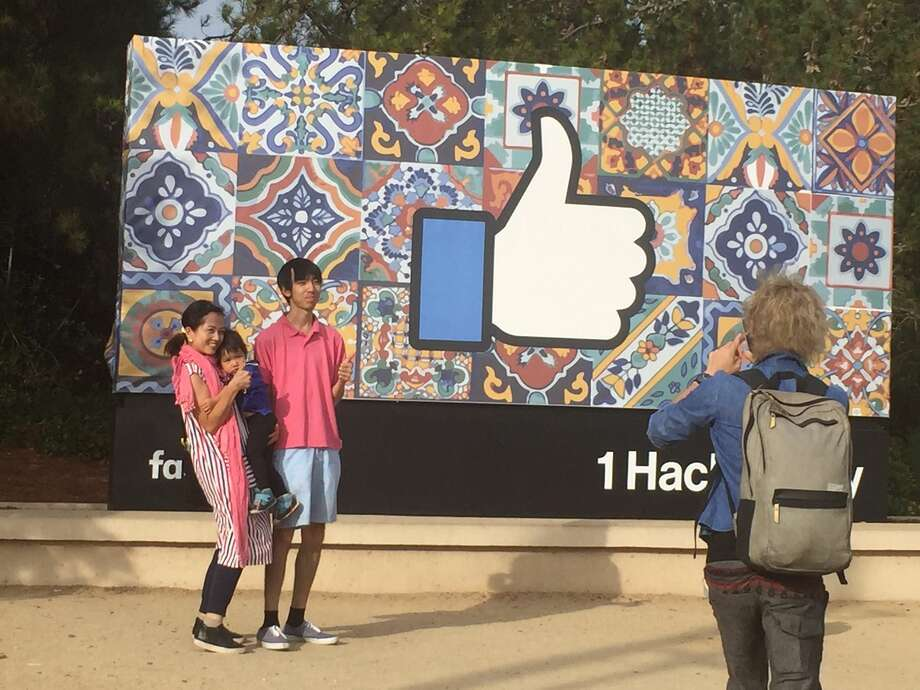 There are only two poses for tourists who visit the new colorful Facebook sign in Menlo Park. The most common one is thumbs up. Photo: Vlae Kershner