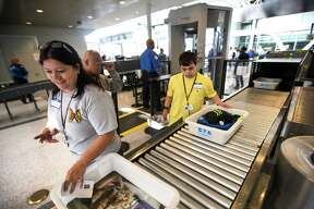 "Maria Rodriguez, left, and Daniel Lozano go through security as part of a Wings for All event at George Bush Intercontinental Airport on Tuesday, Oct. 13, 2015, in Houston. The Arc hosted a Wings for All event, designed to alleviate some of the stress that people with disabilities and their families experience when traveling by air. The children and their families ran through a ""practice"" scenario going through check in, security and boarding an airplane. ( Brett Coomer / Houston Chronicle )"