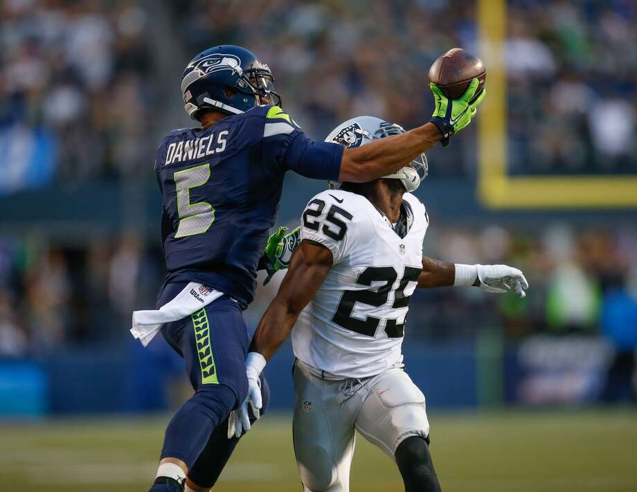 SEATTLE, WA - Wide receiver B.J. Daniels #5 of the Seattle Seahawks wide receiver B.J. Daniels battles cornerback D.J. Hayden #25 of the Oakland Raiders at CenturyLink Field on September 3, 2015. (Photo by Otto Greule Jr/Getty Images)