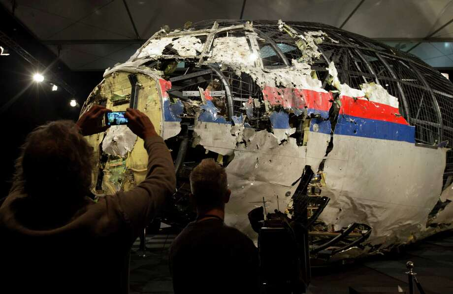 Journalists take images of part of the reconstructed forward section of the fuselage after the presentation of the Dutch Safety Board's final report into what caused Malaysia Airlines Flight 17 to break up high over Eastern Ukraine last year, killing all 298 people on board, during a press conference in Gilze-Rijen, central Netherlands, Tuesday, Oct. 13, 2015. (AP Photo/Peter Dejong) ORG XMIT: PDJ115 Photo: Peter Dejong / AP 2015