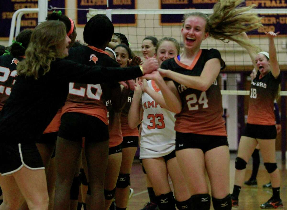Stamford's Liisa Balazs (24) and her teammates celebrate at the conclusion of a varsity girls volletball match against Westhill in Stamford, Conn. on Oct.13, 2015. Stamford sweep Westhill in three sets, 25-13, 25-20, 25-9 to win the city title in girls volleyball.