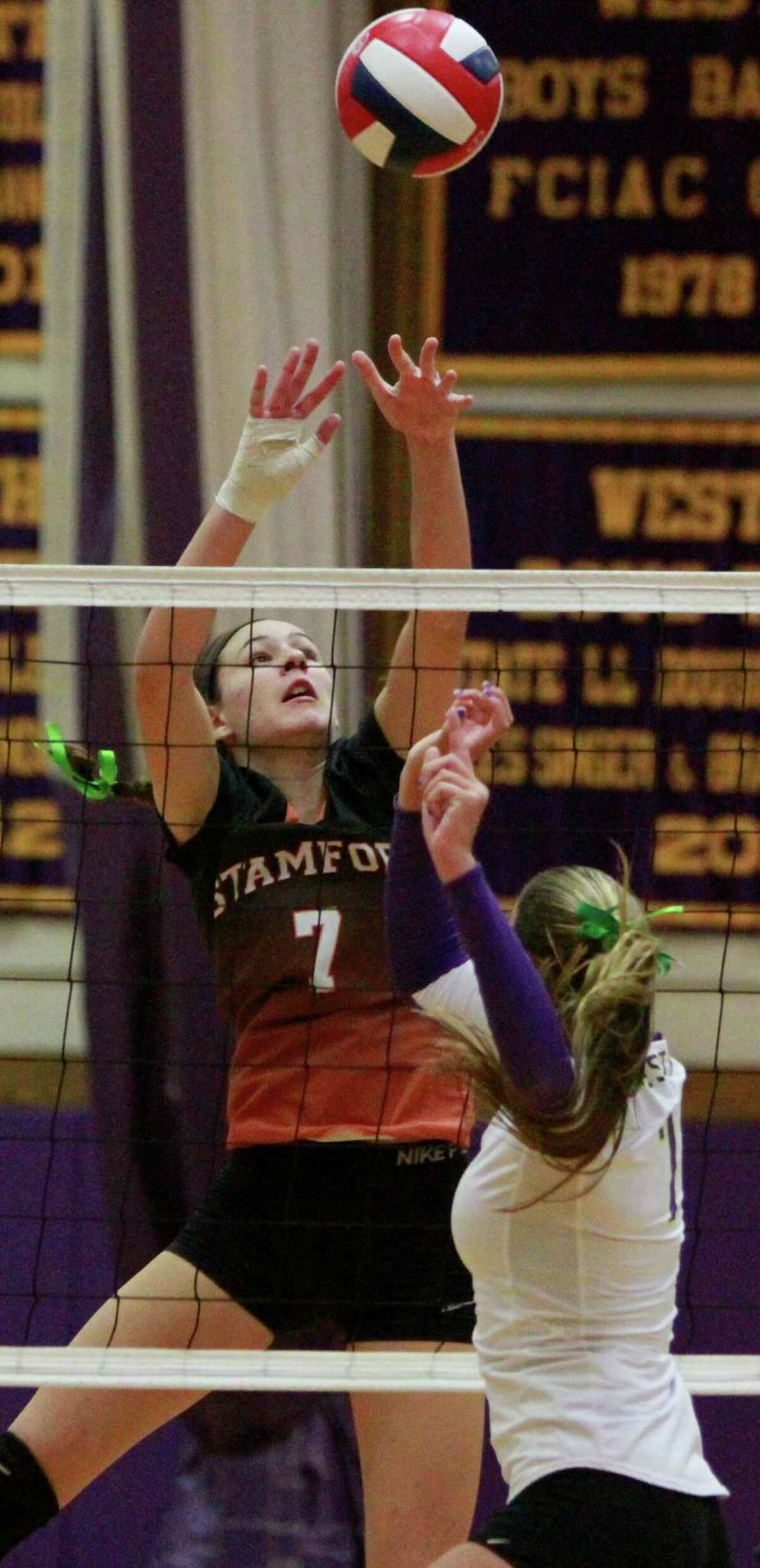 Stamford's Andrea O'Conner taps the ball over the net at Westhill's Haley Liberatore during a varsity girls volletball match in Stamford, Conn. on Oct.13, 2015. Stamford sweep Westhill in three sets, 25-13, 25-20, 25-9 to win the city title in girls volleyball.
