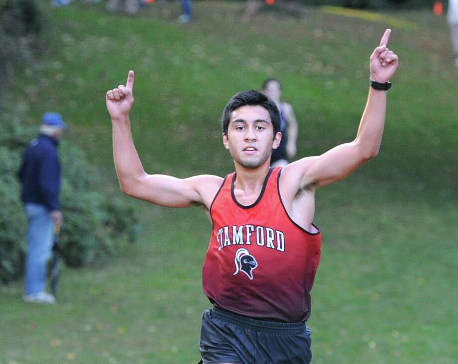 Gilmar Barrios of Stamford High School holds up a pair of number one signs as he crosses the finish line in first place during the was the winner of the boys high school cross country meet at Greenwich Point, Conn., Tuesday, Oct. 13, 2015. Photo: Bob Luckey Jr. / Hearst Connecticut Media / Greenwich Time