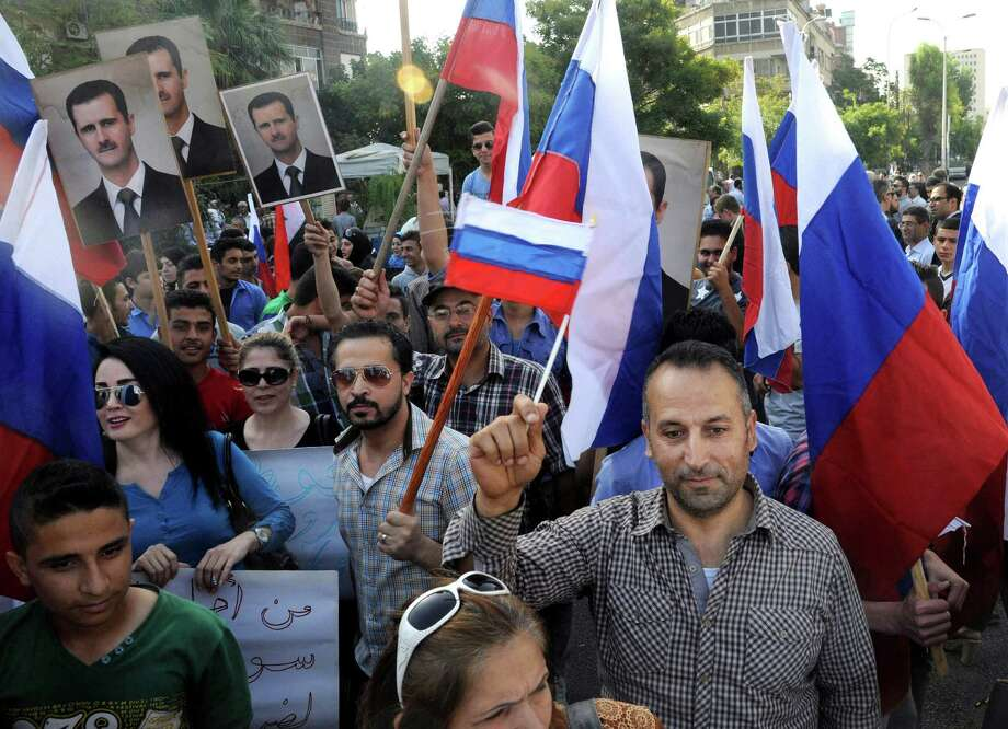 This photo released by the Syrian official news agency SANA, shows Syrians holding photos of Syrian President Bashar Assad and Russian flags, during a protest to thank Moscow for its intervention in Syria, in front of the Russian embassy in Damascus, Syria, Tuesday, Oct. 13, 2015. Insurgents fired two shells at the Russian embassy in the Syrian capital on Tuesday as hundreds of pro-government supporters gathered outside the compound to thank Moscow for its intervention in Syria. (SANA via AP) ORG XMIT: BEI103 Photo: Uncredited / SANA