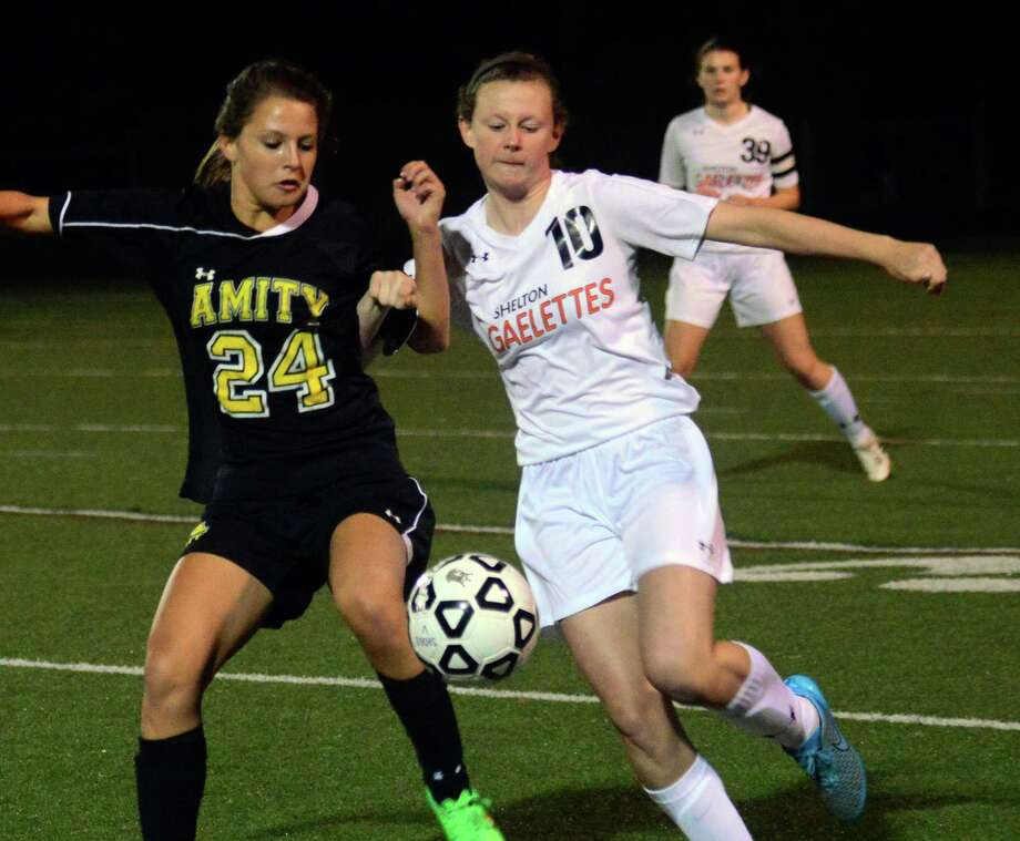 Shelton's Erin Keary, right, and Amity's Kaylee Huber try to intercept the ball during high school soccer action in Shelton, Conn. on Tuesday October 13, 2015. Photo: Christian Abraham / Hearst Connecticut Media / Connecticut Post