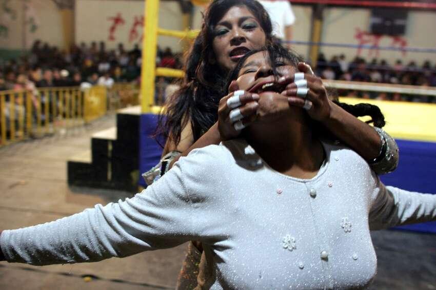 The wrestler Esmeraldo stretches the face of Carmen Rosa during a wrestling match in El Alto, Bolivia.