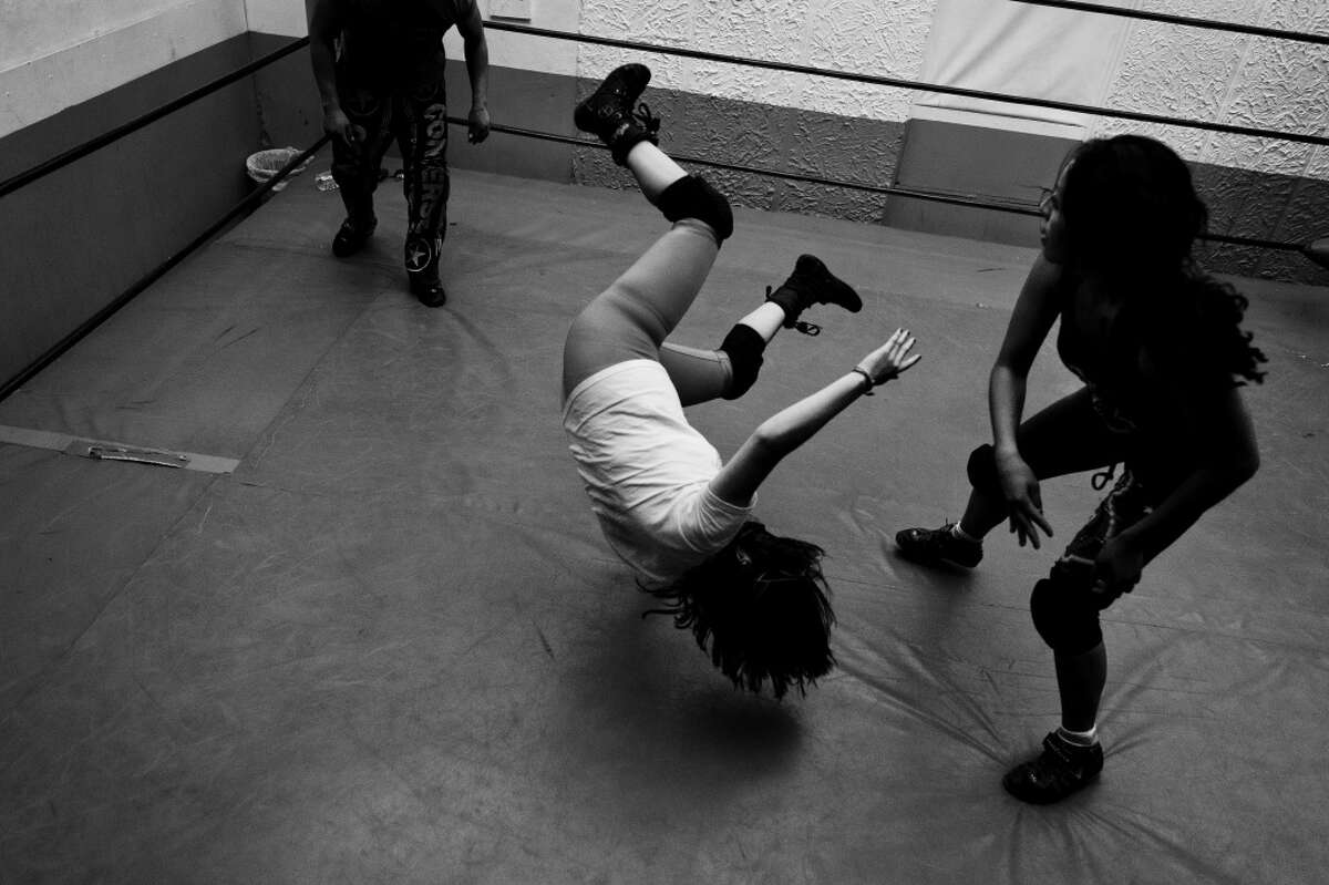 A Lucha libre wrestler throws down her sparring partner during training classes.