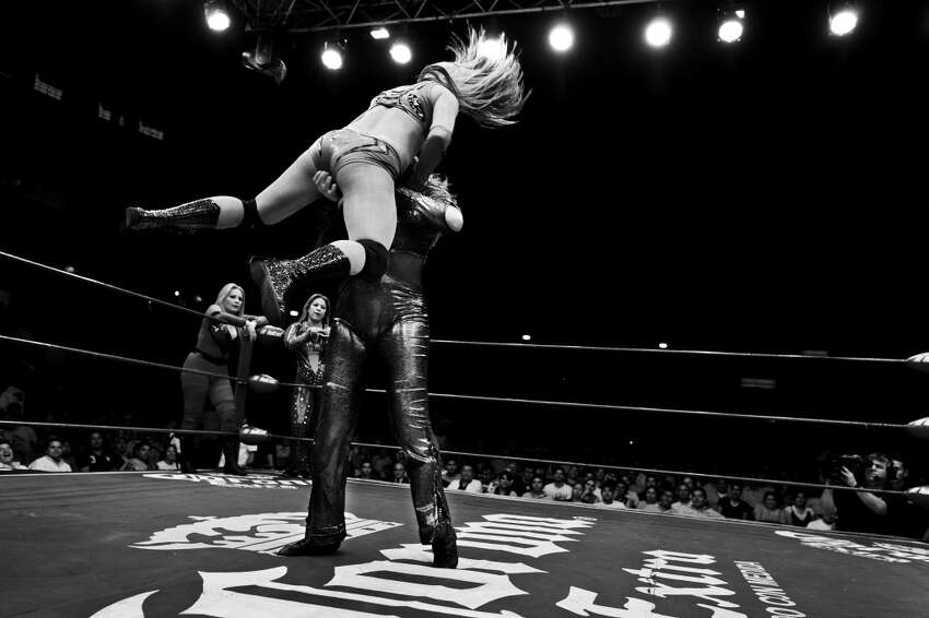 A female Lucha libre wrestler Princesa Blanca holds her rival over the head during a fight at Arena Mexico on April 29, 2012 in Mexico City, Mexico.