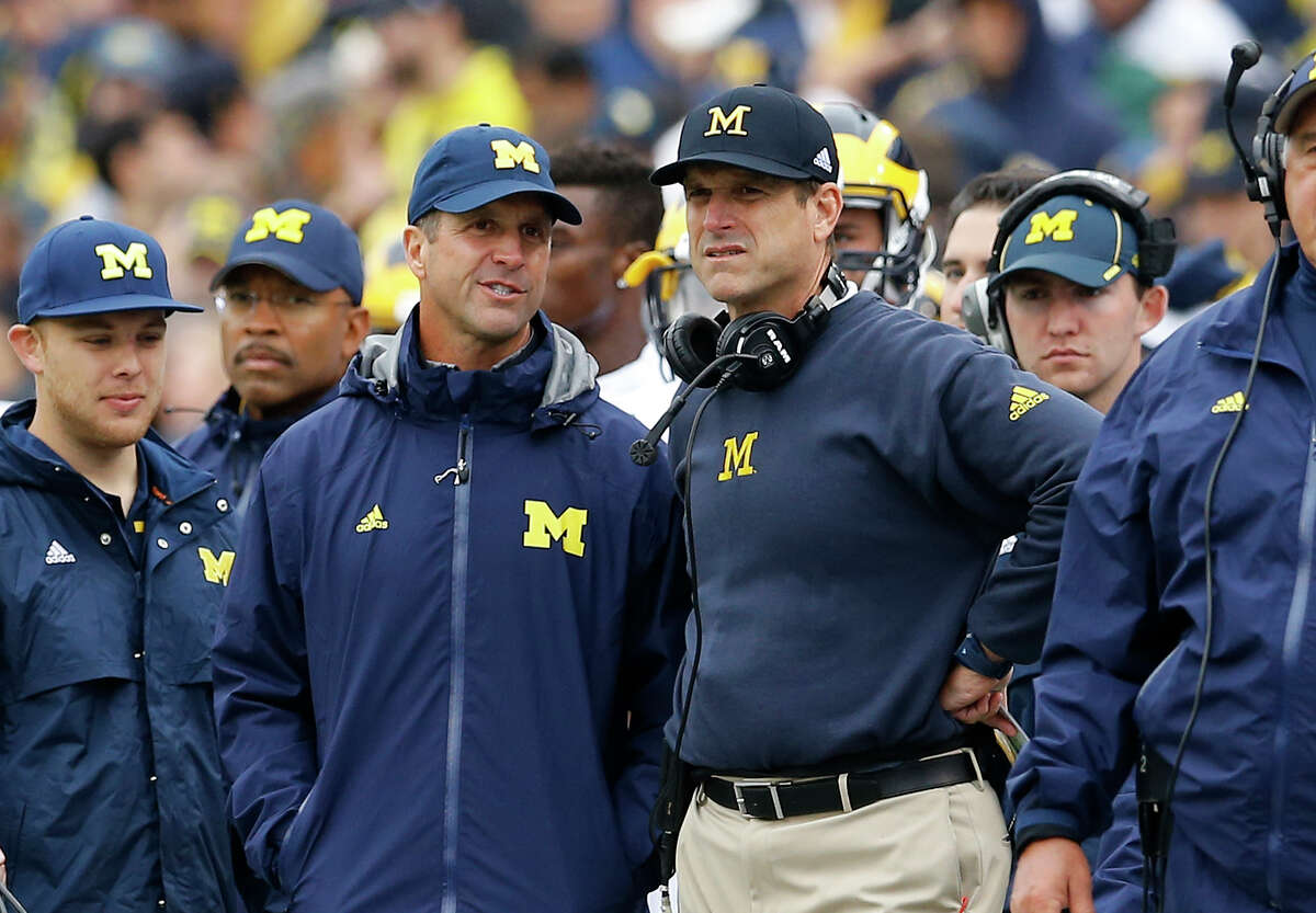 Ravens head coach John Harbaugh (left) speaks with his brother, Michigan head coach Jim Harbaugh, on the sideline in the second half of the Wolverines' 28-0 win at Maryland on Oct. 3.