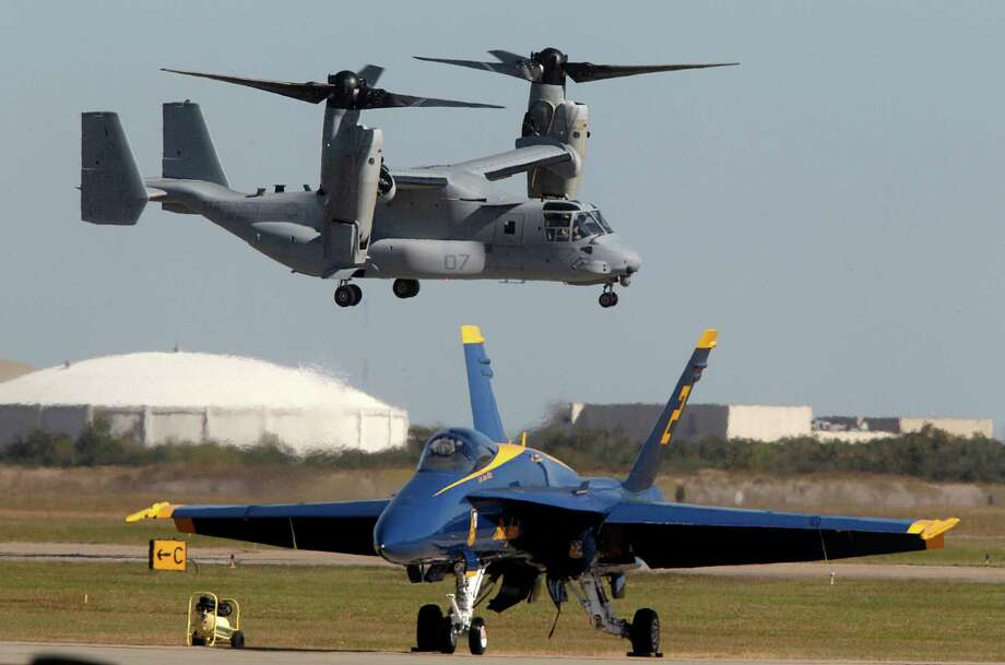 A U.S. Marine Corps. Osprey hovers next to a U.S. Navy Blues Angles jets during Wings Over Houston at Ellington Field on Saturday, Nov. 1, 2014, in Houston. ( Mayra Beltran / Houston Chronicle ) Photo: Mayra Beltran, Staff / © 2014 Houston Chronicle