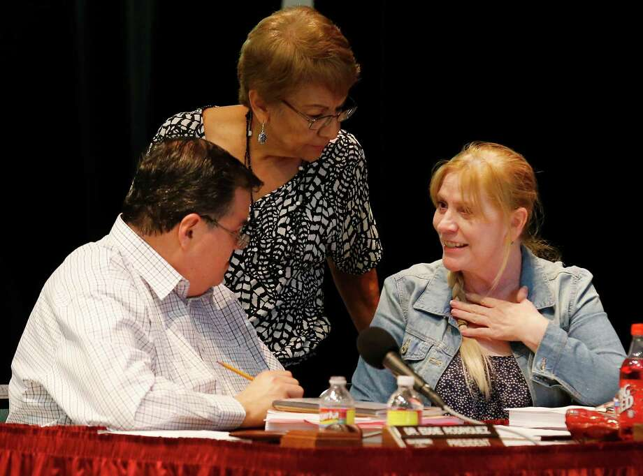 Edgewood ISD school board president Eddie Rodriguez (from left), Secretary Tina Morales and Vice-president Velma Pena chat before going into an executive session during a board meeting in September 2015.  Photo: Kin Man Hui /San Antonio Express-News / ©2015 San Antonio Express-News
