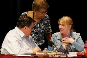 Edgewood ISD school board president Eddie Rodriguez (from left), secretary Tina Morales and vice president Velma Peña chat before going into an executive session during a meeting in September at Edgewood Fine Arts Academy. Their resignations hopelessly deadlocked the board and have caused the TEA to step in.