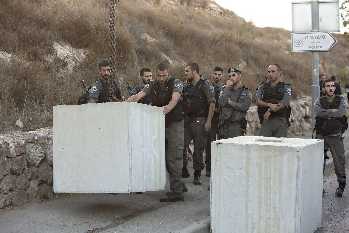 Israeli border police officers help place concrete blocks on the road at the entrance to the east Jerusalem neighborhood of Jabal Mukaber, Wednesday, Oct. 14, 2015. The Israeli military began deploying hundreds of troops in cities across the country on Wednesday to assist police forces in countering a wave of deadly Palestinian shooting and stabbing attacks that have created panic across the country.