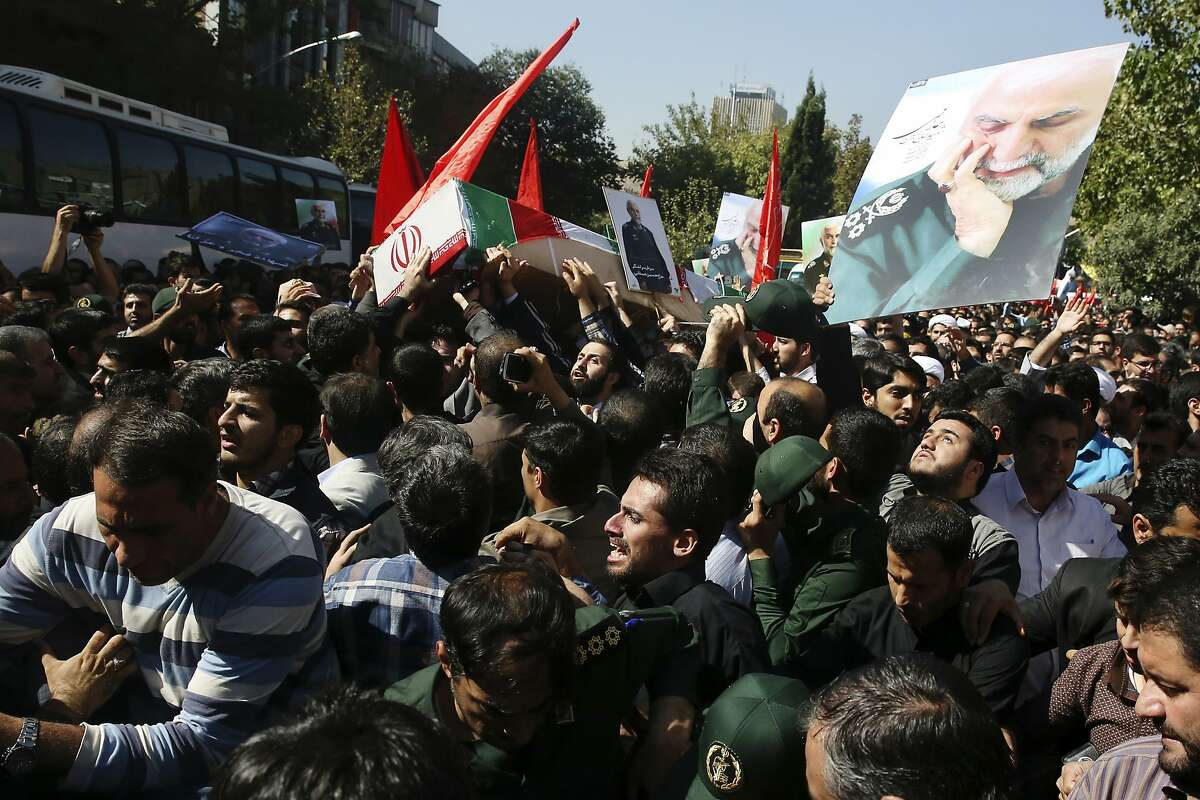 Iranian mourners carry the flag-draped coffin of Revolutionary Guard Gen. Hossein Hamedani, shown in the poster at right, during his funeral ceremony in Tehran, Iran, Sunday, Oct. 11, 2015. Hamedani, a senior commander of the Guard, was killed by Islamic State extremists last week near the Syrian city of Aleppo, according to a state TV report.