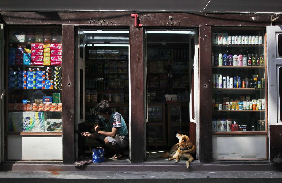 In this Tuesday, Oct. 13, 2015 photo, A Nepalese man paints a shop as a dog sits at the entrance in Thamel, the tourist hub in Kathmandu, Nepal. Just when Nepal was recovering from the devastating earthquake that killed thousands, flattened hundreds of thousands of houses and chased away foreign tourists, protests by ethnic groups and severe fuel shortages are again keeping visitors away from the nation known for highest peaks in the world. In Thamel, where tourists walked shoulder to shoulder along the narrow alley lined with stores for trekking gear, souvenirs, cafes and restaurants, there is only a thin presence of visitors.