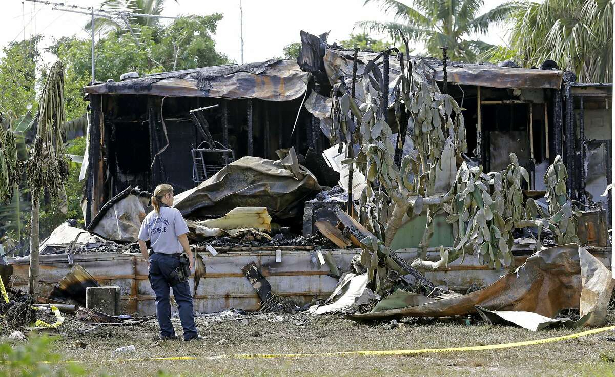 A Palm Beach County Fire Rescue worker looks at a mobile home where a small plane crashed, Wednesday, Oct. 14, 2015, in Palm Springs, Fla. Two mobile homes were set on fire, killing the pilot and a 21-year-old woman who was inside one of the homes. No one else was aboard the plane and no one else on the ground was injured when the plane plunged from the sky Tuesday into athe park of a few dozen mobile homes, National Transportation Safety Board investigator Dan Boggs said at a news conference.