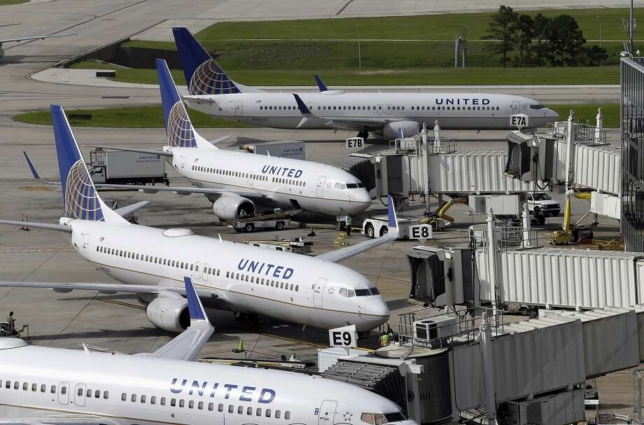 United Airlines planes are parked at their gates as another plane, top, taxis past them at George Bush Intercontinental Airport in Houston. Photo: David J. Phillip, Associated Press