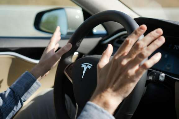 Reporter David Baker takes his hands off the steering wheel as the Tesla drives in autopilot in Palo Alto, Calif. on Wednesday, Oct. 14, 2015. An update to Tesla's Autopilot system will aide drivers in changing lanes, parking and steering.