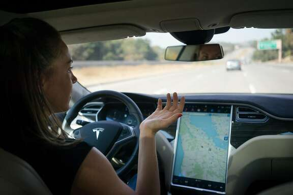 Khobi Brooklyn drives a Tesla on autopilot on the freeway in Palo Alto, Calif. on Wednesday, Oct. 14, 2015. An update to Tesla's Autopilot system will aide drivers in changing lanes, parking and steering.