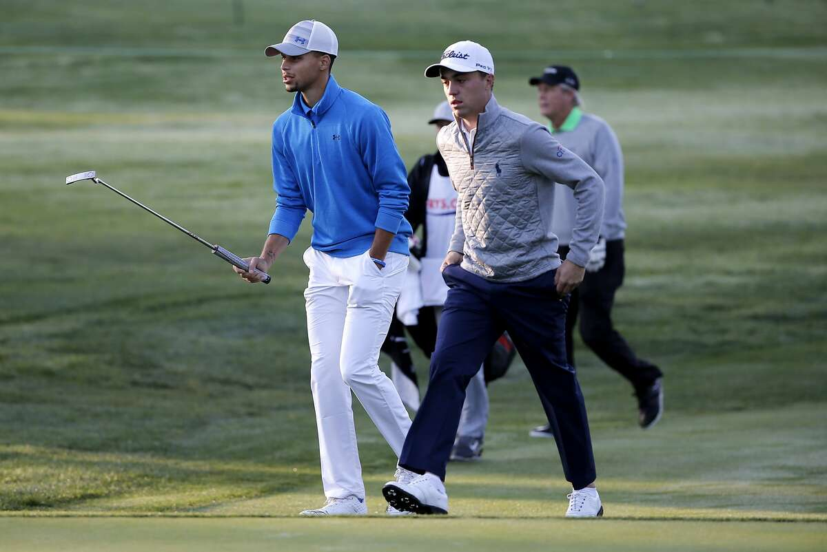 Warriors' Stephen Curry walks up the 1st fairway with pro Justin Thomas during the Fry's.com Pro-Am at Silverado Resort in Napa, Calif., on Wed. October 14, 2015.