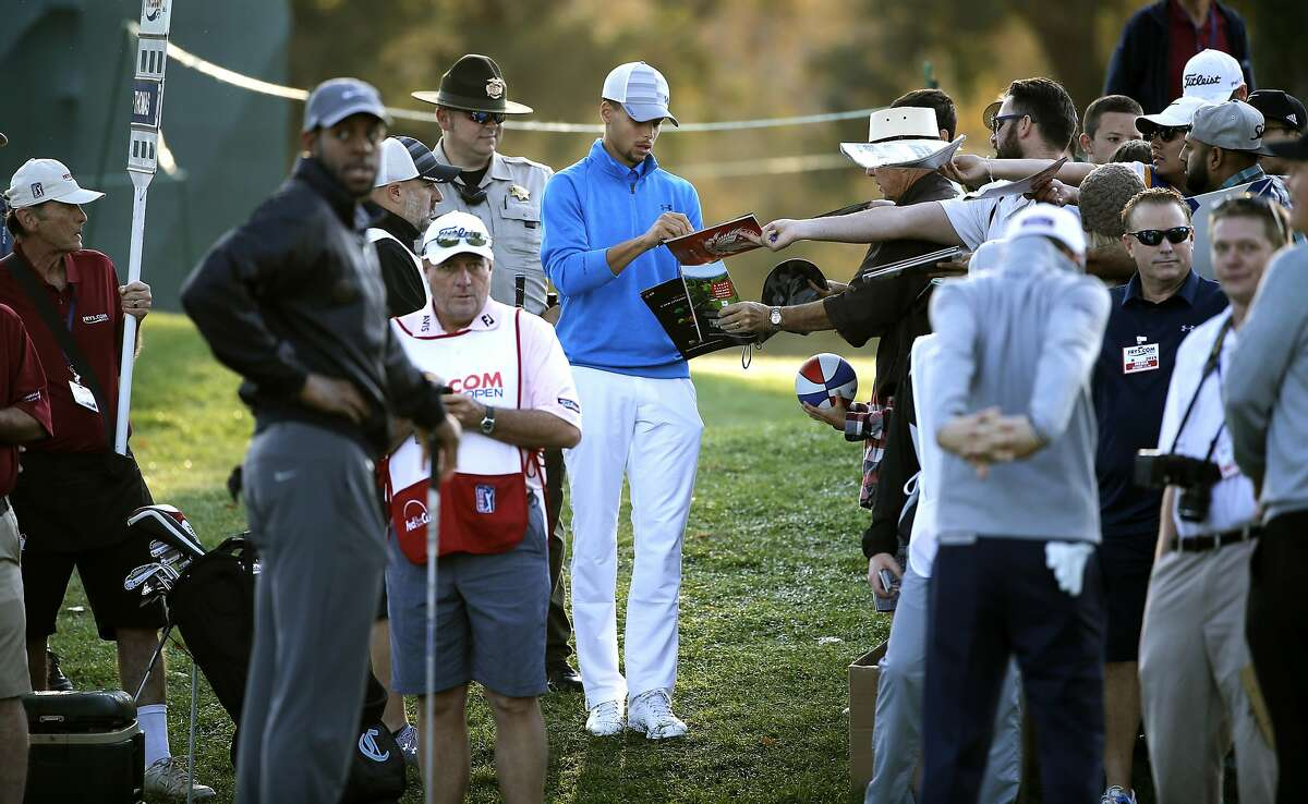 Warriors' Stephen Curry, (center) signs for fans during the Fry's.com Pro-Am at Silverado Resort in Napa, Calif., on Wed. October 14, 2015.