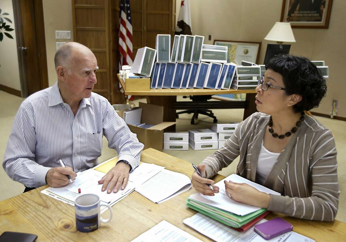 CORRECTS SPELLING OF FIRST NAME TO GRACIELA, INSTEAD OF GARCIELA - California Gov. Jerry Brown discusses a bill he is about to sign with Graciela Castillo-Krings, his deputy legislative secretary, at his Capitol office in Sacramento, Calif., Friday Oct. 9, 2015. Brown has until Sunday to deal with the hundreds of bills passed by lawmakers in the final days of this year's legislative session. (AP Photo/Rich Pedroncelli)