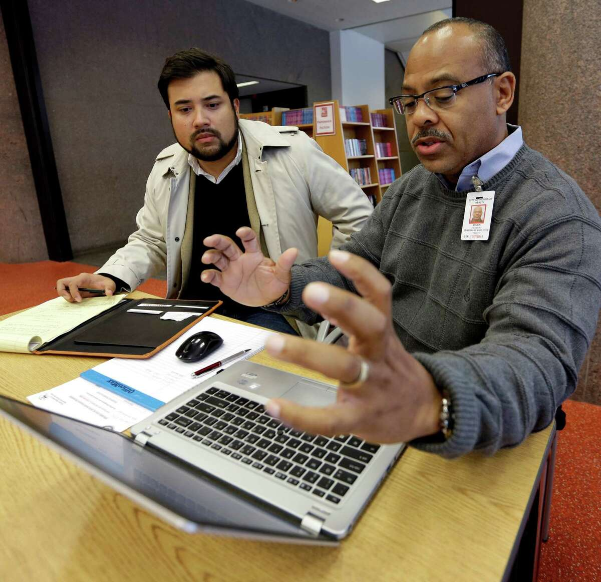 Herb Shook, right, helps David Ortez of Houston get information on the Affordable Care Act last year.