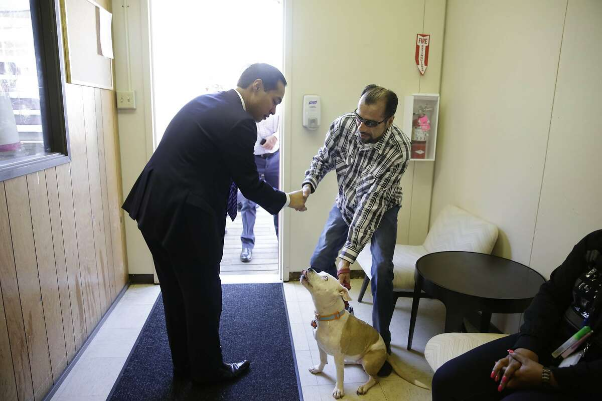 Housing and Urban Development Secretary Julian Castro (left) shakes the hand of Enrique Gonzalez (right) as Gonzalez introduces his dog Ahnoni as Castro tours the San Francisco Navigation Center with Mayor Ed Lee and others on Wednesday, October 14, 2015 in San Francisco, Calif.