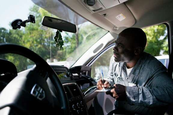 Robert Kyamusugulwa writes down the number of his EZ TAG as part of the signing up process to become a Get Me driver, which is a new delivery and driver service. Tuesday, Oct. 13, 2015, in Houston.