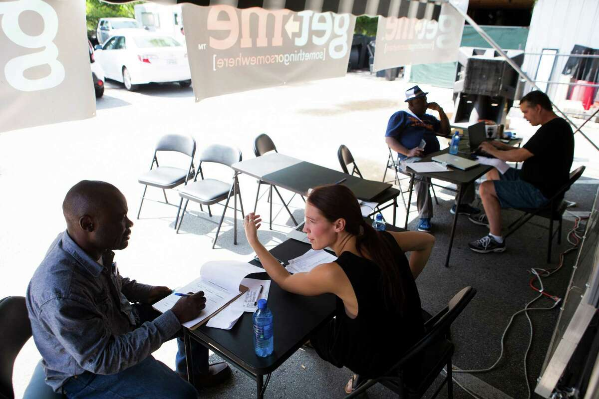 Megan Momk, a staff member of Get Me a new delivery and driver service, trains Robert Kyamusugulwa, left, who is interested in becoming a Get Me driver on Oct. 13.