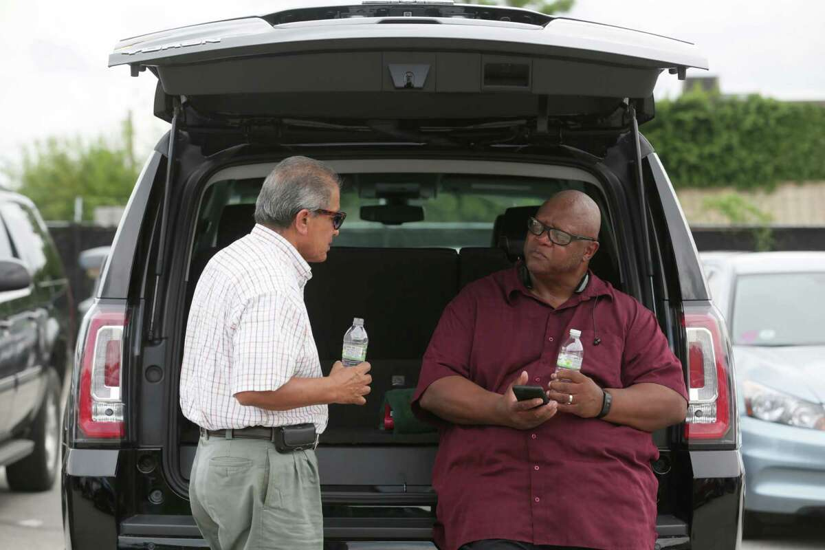 Khalid Faruki, left, talks with Darnell Robinson, both drivers for Uber, as they wait for passengers, in the TNC lot just outside of George Bush Intercontinental Airport on Sept. 9, 2015.