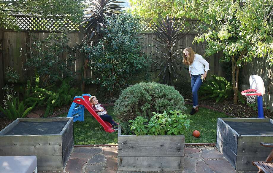 Interior designer Jennifer Jones and son, Owen, show the yard at their S.F. home. Photo: Liz Hafalia, The Chronicle
