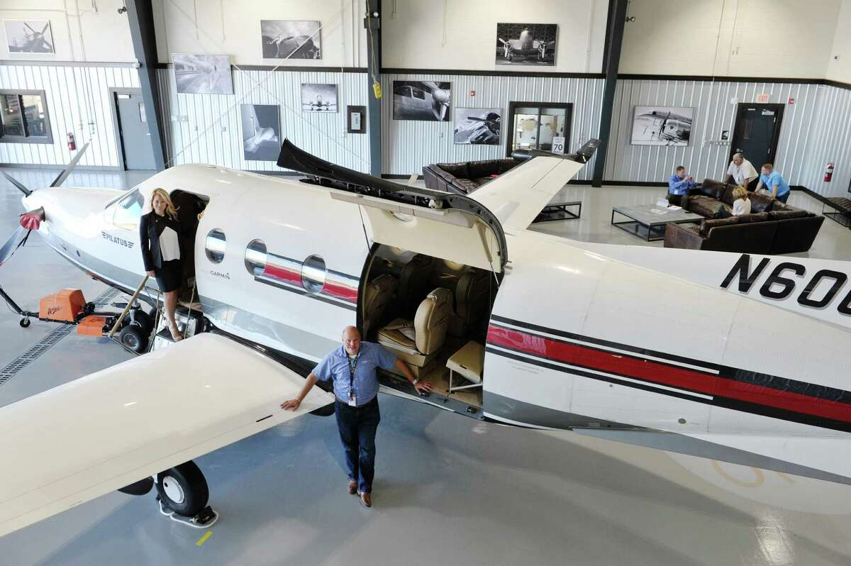 Diane Meyer, left, interior designer and manager of special events at IntegraOptics and company CEO David Prescott pose for a photograph in the hanger which is also a meeting space lounge on Thursday, Oct. 8, 2015, in Latham, N.Y. (Paul Buckowski / Times Union)
