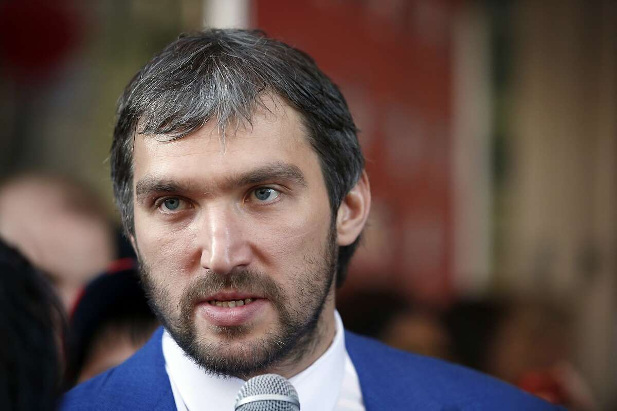 Washington Capitals left wing Alex Ovechkin (8), from Russia, talks with a reporter after walking a red carpet before their season opening NHL hockey game against the New Jersey Devils, Saturday, Oct. 10, 2015, in Washington. (AP Photo/Alex Brandon)