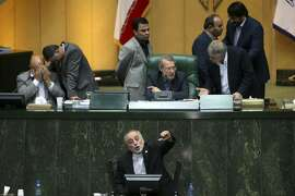 Head of Iran's Atomic Energy Organization Ali Akbar Salehi, bottom, speaks in an open session of parliament while discussing a bill on Iran's nuclear deal with world powers, in Tehran, Iran, Sunday, Oct. 11, 2015. Iran's official IRNA news agency reported Sunday the country's parliament has approved an outline of a bill that allows the government to implement a historic nuclear deal reached between Iran and world powers. (AP Photo/Ebrahim Noroozi)