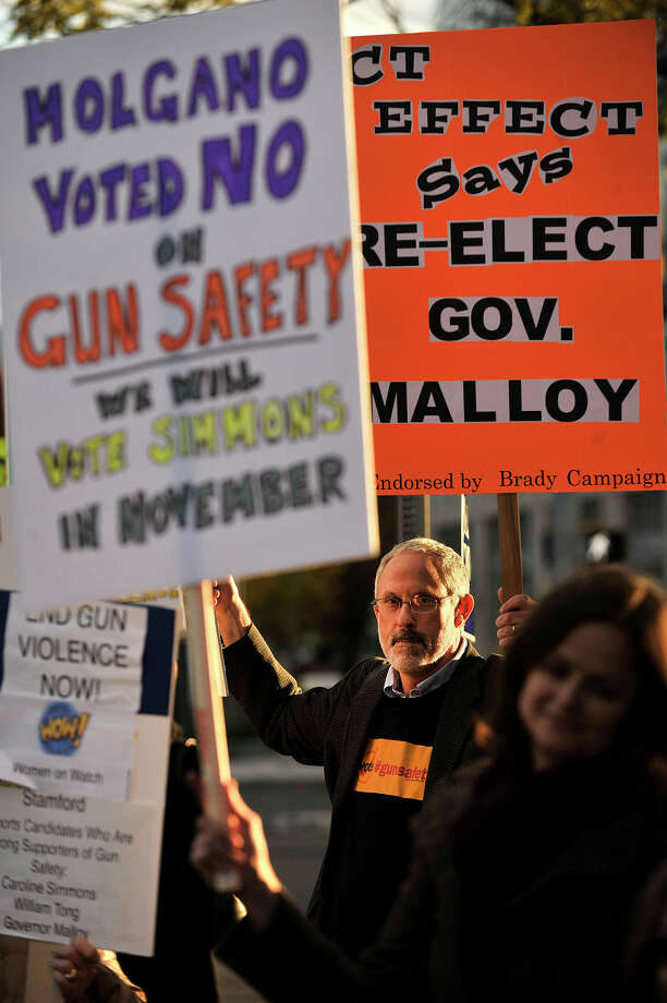 Jonathan Perloe, with the Greenwich Council Against Gun Violence, holds a sign amid others during a protest in support for reasonable gun safety laws lsat October. A Volkswagen owner, he was so angry at hearing the company had been cheating on its admission tests that he started a business to produce bumper stickers letting the international organization know how he and other VW owners felt. Photo: Jason Rearick / Jason Rearick / Stamford Advocate