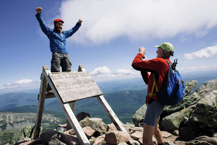Tom Buononato, left, and William Young celebrate upon reaching the summit of Mount Katahdin in Maine, the iconic northern terminus of the Appalachian Trail on Aug. 14. Faced with increasing crowds and partylike behavior by a few, officials are threatening to reroute the end of the trail off Katahdin -- a proposal that has stunned the hiking world. Photo: TRISTAN SPINSKI /New York Times / NYTNS