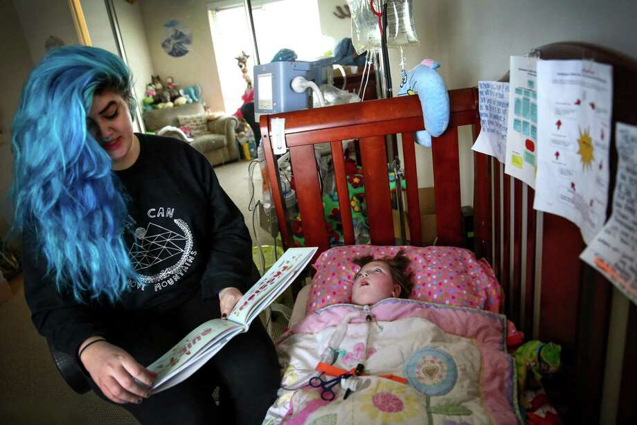 Teal Victoria reads to her 3-year-old daughter Kai at their northeast Seattle home Tuesday. Kai is on a ventilator and is cared for around the clock at home by her mother and her nurses. Photo: JOSHUA TRUJILLO, SEATTLEPI.COM / SEATTLEPI.COM