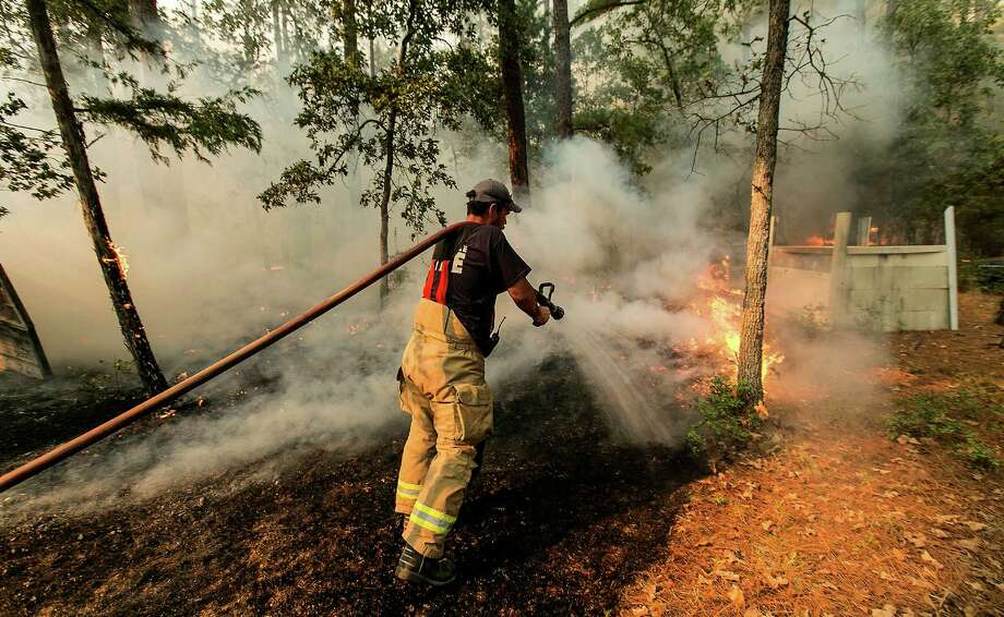 The soaring 100-degree temperatures and the lack of measurable rainfall for much of this summer have nearly 80 Texas counties enacting an outdoor burn ban. Five of those counties are within the San Antonio Metro region. In this photo, Smithville firefighter Mike Parnell uses a hose to put out hotspots of the Hidden Pines Fire burning at the end of Keller Road near Smithville, Texas, on Wednesday, Oct. 14, 2015. Photo: Rodolfo Gonzalez, Associated Press / Austin American-Statesman