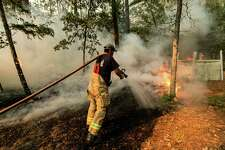 Smithville firefighter Mike Parnell uses a hose to put out hotspots of the Hidden Pines Fire burning at the end of Keller Road near Smithville, Texas, Wednesday, Oct. 14, 2015. The Texas A&M Forest Service says challenging topography and uncontrolled fire lines has slashed the containment of the Bastrop County fire to 10 percent as night fell Wednesday. The Forest Service had estimated 50 percent containment earlier Wednesday. (Rodolfo Gonzalez/Austin American-Statesman via AP) AUSTIN CHRONICLE OUT, COMMUNITY IMPACT OUT, INTERNET AND TV MUST CREDIT PHOTOGRAPHER AND STATESMAN.COM, MAGS OUT; MANDATORY CREDIT