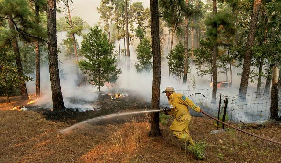 Smithville firefighter Birt Mikulec pulls a line as he races to put water on hotspots of the Hidden Pines Fire burning at the end of Keller Road near Smithville, Texas, Wednesday, Oct. 14, 2015. The Texas A&M Forest Service says challenging topography and uncontrolled fire lines has slashed the containment of the Bastrop County fire to 10 percent as night fell Wednesday. The Forest Service had estimated 50 percent containment earlier Wednesday. (Rodolfo Gonzalez/Austin American-Statesman via AP)  AUSTIN CHRONICLE OUT, COMMUNITY IMPACT OUT, INTERNET AND TV MUST CREDIT PHOTOGRAPHER AND STATESMAN.COM, MAGS OUT; MANDATORY CREDIT Photo: Rodolfo Gonzalez, Associated Press / Austin American-Statesman