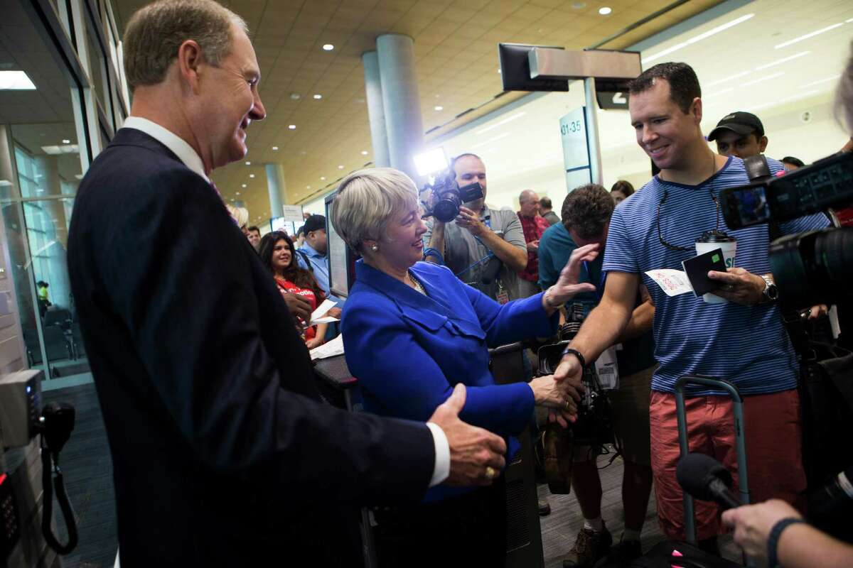 Gary Kelly, chairman, president and CEO of Southwest, greets and accept the boarding pass of Southwest passenger accompanied by Houston Mayor Annise Parker during the inauguration of the Southwest Airlines' international concourse at Hobby Airport, Thursday, Oct. 15, 2015, in Houston.