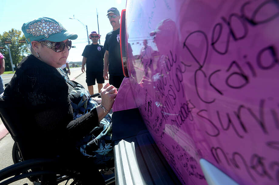 Robbie Reeves signs the survivor's message space on the back of one of the pink painted vehicles in the Pink Heals Tour, which made a stop in Silsbee Wednesday. Reeves is on leave from her job as principal at Kirby Elementary School as she continues to battle uterine cancer, which has spread throughout her body. Tuesday, she had neurosurgery to radiate tumors that were found in her brain, and was glad to be able to come out and add her message of hope to the tour. The national tour helps raise money for cancer research, which is given to each state in which the funds were raised. The non-profit group supports local efforts to battle cancer and assist those struggling with the disease. The caravan of pink fire trucks and other vehicles made a stop at Read Turrentine Elementary before heading to Community Bank, where it would remain open to the public throughout the afternoon. Photo taken Wednesday, October 14, 2015 Kim Brent/The Enterprise Photo: Kim Brent / Beaumont Enterprise