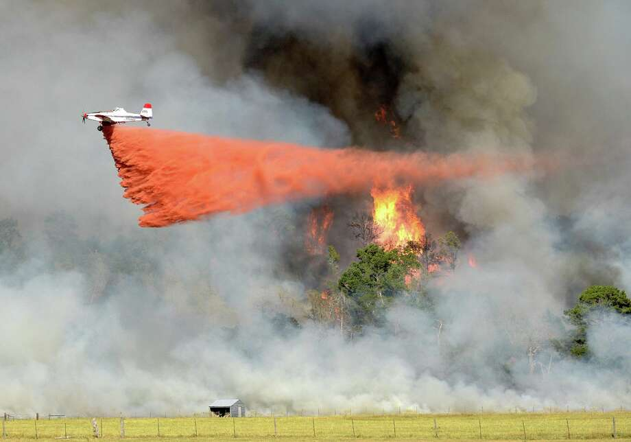 Fire fighting aircraft release a mixture of water with ammonium phosphate or sulfate at the Lonesome Pines Ranch located just north of Buescher State Park. The mixture is more of a fire retardant than a fire extinguisher. Photo: Chase Fountain, Courtesy Of The Texas Parks And Wildlife / CHASE A. FOUNTAIN, TPWD