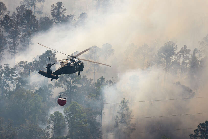 A Texas Army National Guard UH-60 Blackhawk out of the Austin Army Aviation Facility helps fight wild fires threatening homes and property near Bastrop, Texas, Oct. 14, 2015.