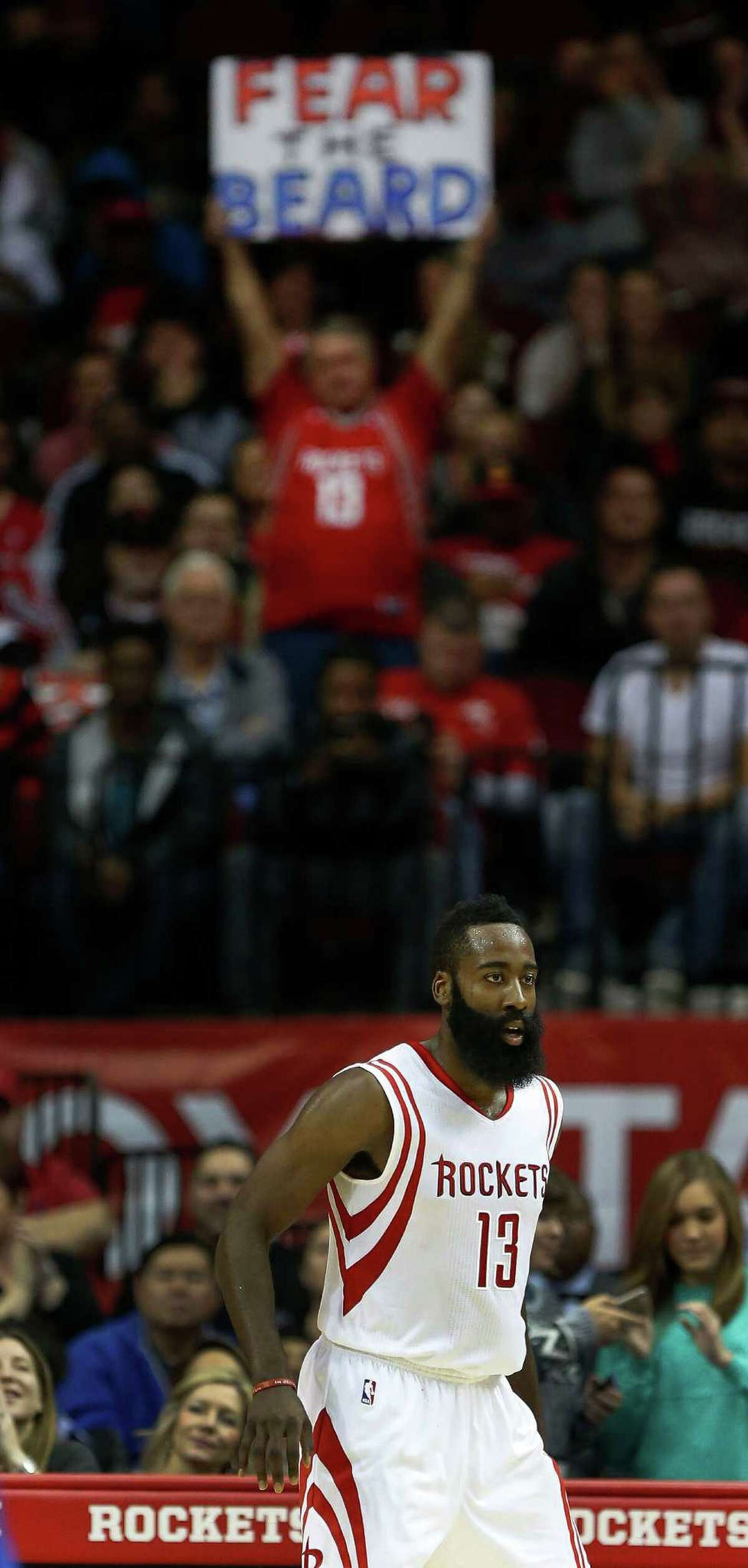 """A Houston Rockets fan flashes a """"Fear the Beard"""" sign after one of hi three-pointers during the second half of an NBA basketball game at Toyota Center, Monday, Nov. 24, 2014, in Houston. ( Karen Warren / Houston Chronicle )"""