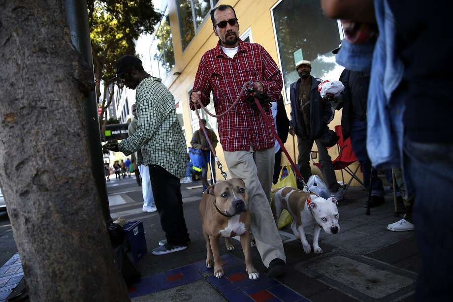 Veteran Enrique Gonzalez walks his dogs, Vlad and Ahnania, back to the Navigation Center. Photo: Scott Strazzante, The Chronicle