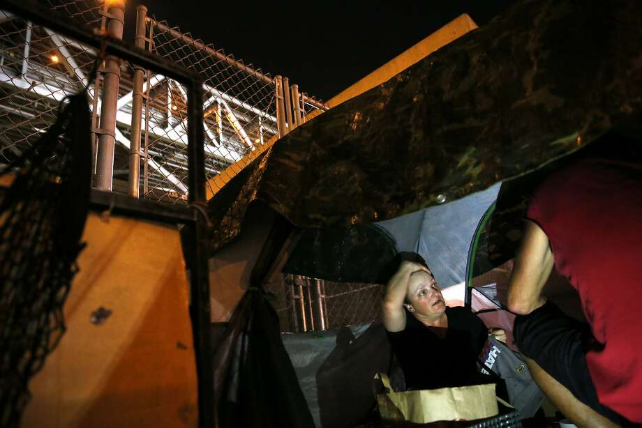 Joanna Silver and James Kelly prepare to bed down for the night in their tent on Bryant Street in San Francisco. Photo: Scott Strazzante, The Chronicle