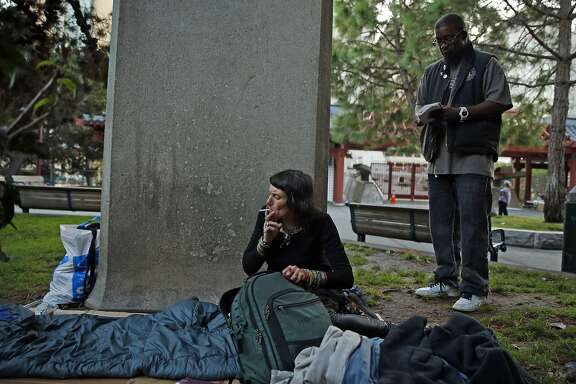 SF Homeless Outreach Team's Hugh Gregory waits for homeless woman Katrina Newsome to finish her cigarette before helping her relocate from Portsmouth Square to the Navigation Center in the Mission District in San Francisco, Calif., on Tuesday, October 13, 2015.