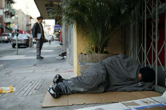 A homeless man sleeps on the sidewalk, as SF Homeless Outreach Team's Pau Liu unsuccessfully tries to convince another homeless man to relocate to the Navigation Center in San Francisco, Calif., on Tuesday, October 13, 2015.